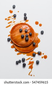 Hot pancakes with scattered blueberries and sprinkled maple syrup. The good-looking and good-for-you breakfast. Vertical top view.