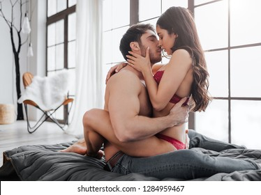Hot passionate couple sitting on bed in room and kissing. She sit on him and embrace with legs. Guy touch her naked back and bring forward.