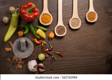 Hot peppers, seeds, spices and molcajete on a dark wooden table top view