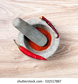 Hot peppers and spicy paprika powder with stone mortar kitchen and pestle.