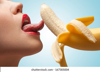 The hot photo of girl lower face going to lick a banana she holds.