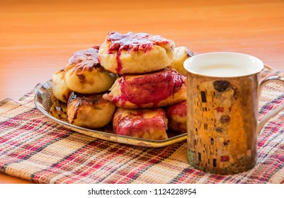 "hot pie with berries, fried in oil, lined in a dish, a mug of cold milk with Klimt ""the kiss"", on a napkin"