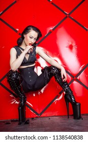 hot pin up kinky woman wearing black harness and shiny fetish thigh high boots on red background alone