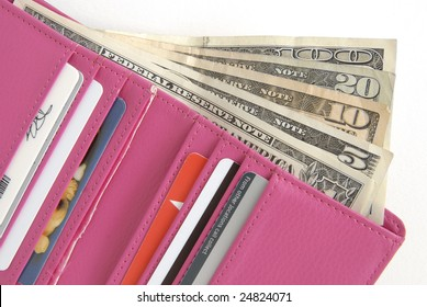 Hot Pink wallet is filled with credit cards and lots of cash, on a white background.