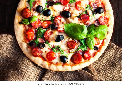 Hot pizza with Pepperoni Sausage on a dark background, top view.  Pizza on the black table with copy space