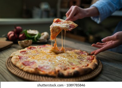 Hot pizza slice with melting cheese on a rustic wooden table. Food ingredients and spices for cooking. Mushrooms, tomatoes, cheese, onion, oil, pepper, salt, basil, olive and delicious italian pizza.