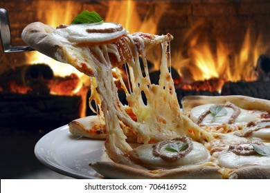 Hot pizza slice with melting cheese with wood oven in background.