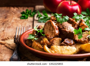 Hot pork stew with apple slice on the plate, vintage wooden kitchen table background, selective focus