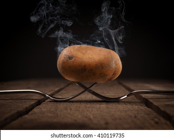 Hot potato with big steam on two steel forks on a rustic wooden table