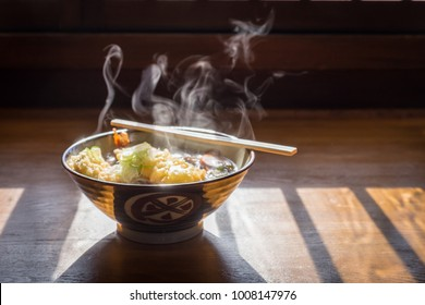 Hot ramen with tempura and smoke float over the bowl under nature sunlight.