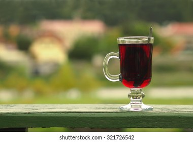 Hot red beverage in a glass cup lying outdoor on a green wooden board.