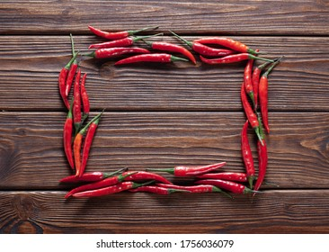 hot red chilli pepper in pods in the shape of a rectangle on wooden table