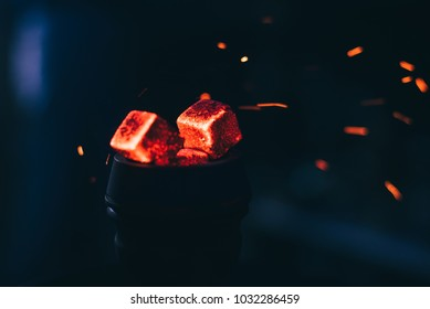 hot red coals with hookah sparks in metal bowl for Shisha Smoking and traditional Asian relaxation close up