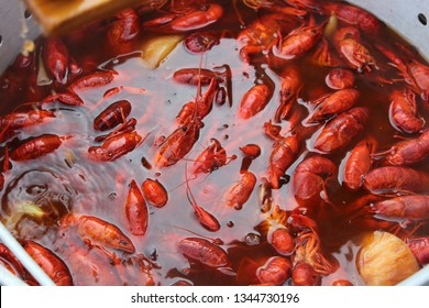 Hot, red, Louisiana crawfish boiling in a pot with corn, onions, and lemon.