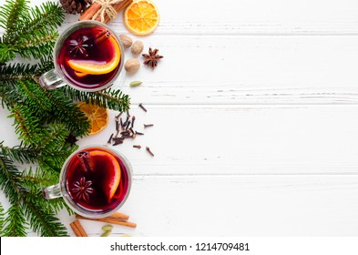 Hot red mulled wine in glass with orange, cinnamon sticks and star anise with ingredients on white wooden background. Two spicy warm beverages. Seasonal Christmas mulled drink. Copy space. Top view.