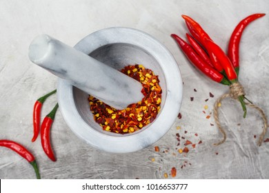 Hot red pepper flakes in a marble mortar and peppercorns on stone table. Copy space