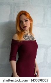 Hot red-haired girl with tattoo in burgundy dress