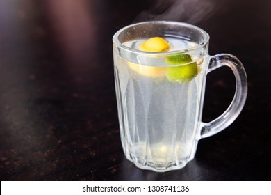 Hot refreshing calamansi lime juice in drinking glass against dark background