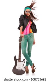 hot rock and roll woman wearing high heels shoes, with windy hair, holding her electric guitar on the ground, on white background