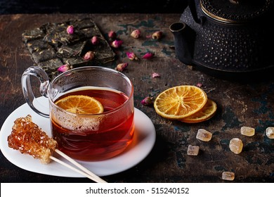 Hot Roiboos tea served in the glass cup decorated with variety of different dry tea, sugar candies and dry oranges