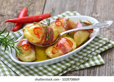 Hot rosemary potatoes stuffed with cheese and wrapped in South Tyrolean bacon, baked in olive oil with chili slices