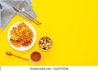 Hot round waffles ready to eat. Belgian recipe. Waffles on plate near honey and dried fruits on yellow background top view copy space