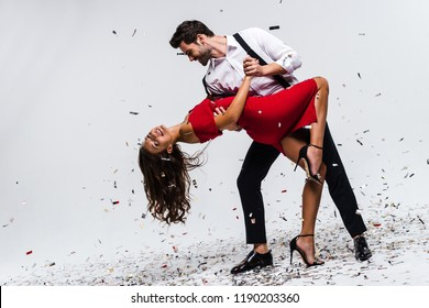 It is hot salsa! Full length of young beautiful couple dancing while standing against white background with confetti