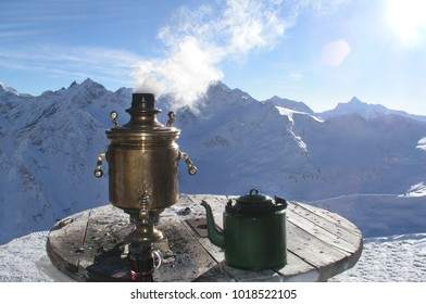 Hot samovar and teapot, on a table on the background of a snowy mountain. Elbrus, Europe, Russia, the Caucasus, Kabardino-Balkaria, Karachay-Cherkessia.