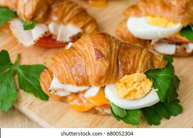 Hot sandwich with mini croissant, egg, parsley, melted cheese, chicken ham, tomato on wooden cutting board. Healthy starter