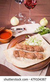 hot sausage with onion,spicy sauce and fresh parsley in dish