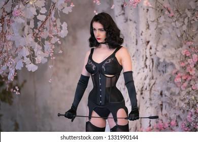 hot sex mistress in black retro lingerie posing on white tree background