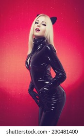 Hot sexy blonde girl with red lips makeup in cat woman style black fetish latex pvc catsuit