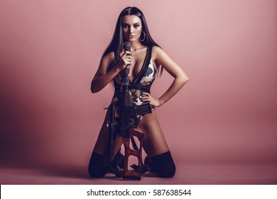 Hot and sexy brunette girl with a gun on a pink background. Beautiful girl in the army.