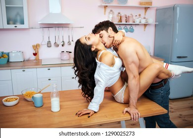 Hot sexy couple having intercourse on table. Young woman sit there and enjoy. Guy stand close and kiss. Breakfast stand on table.