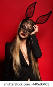 Hot and sexy fashion portrait of a girl posing in a lace like bunny. Red background. Submissive in black outfit.  Vertical