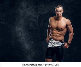 Hot sexy fit man is taking off his wetsuit in dark photo studio.