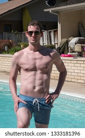 Hot sexy guy with no shirt and hot body standing next to an outdoor swimming pool in the summer sun in aviator sunglasses looking cool and confident. Man with great body posing next to swimming pool.