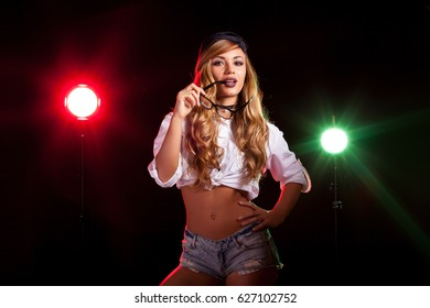 Hot sexy woman in white shirt with two lights from behind in studio photo on black background