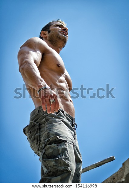 Hot, shirtless, muscular construction worker shirtless seen from below against blue sky