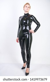 hot short hair female wearing black fetish costume made from latex rubber. young strong woman in kinky sexy outfit on white studio background alone. curvaceous girl in shiny and reflective  jumpsuit.