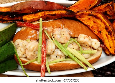 Hot shrimp poboy with sweet potato fries and pickle spears.