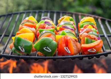 Hot skewers on grill with vegetables and meat