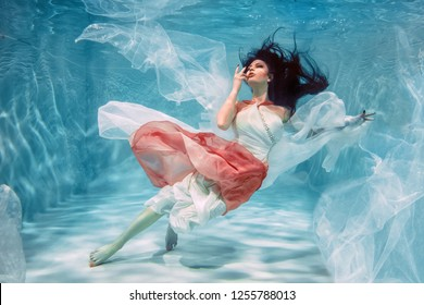 Hot Slim Brunette Woman Posing Under water in beautiful clothes alone in the deep