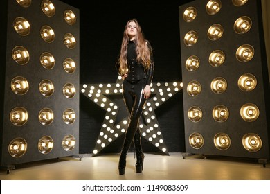 hot slim woman posing in latex rubber fashion clothes on black background with yellow lights bulbs