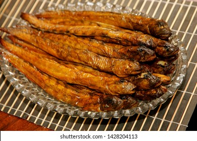 Hot smoked eelpouts or viviparous blenny on a glass plate and wooden table background. Latvian smoked fish