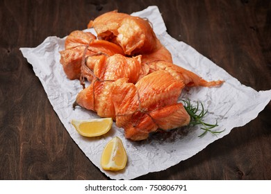 hot smoked salmon fillet rolls on crumpled paper with lemon and greens