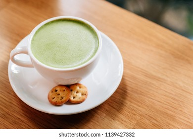 Hot and smooth green tea latte with froth served in white ceramic cup with biscuits