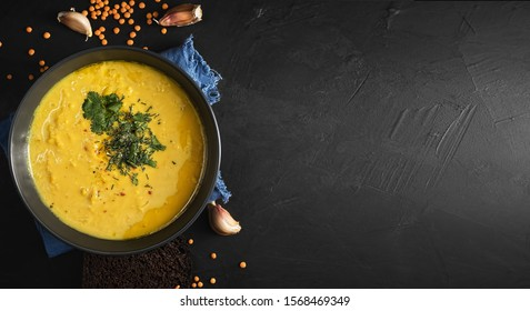 Hot soup with red lentils, spices, herbs, vegetables, lemon and cream. Soup on a blue napkin, next to garlic cloves. Lentil seeds are scattered on a black background. Top view. Copy space for text.