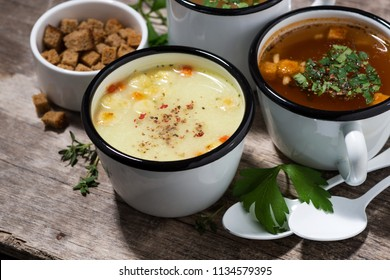 hot soups in mugs on wooden table, top view