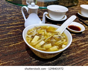 Hot and sour soup with bean curd and Enoki mushroom. Vinegar can be added to taste.